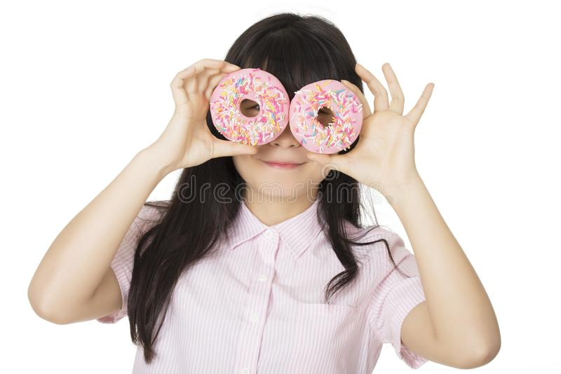 Asian woman having some fun with delicious strawberry frosted donuts stock photo