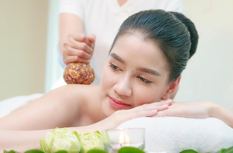 Asian woman having Thai herbal compress massage in spa env stock images
