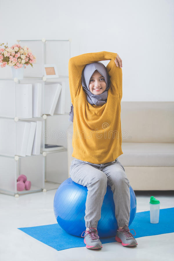 Asian woman with head scarf doing exercise at home stock photos
