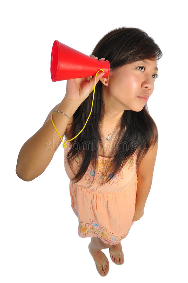 Asian Woman hearing through a red cone. Beautiful young Asian Woman picture taken from the top to give a big doll head effect royalty free stock images