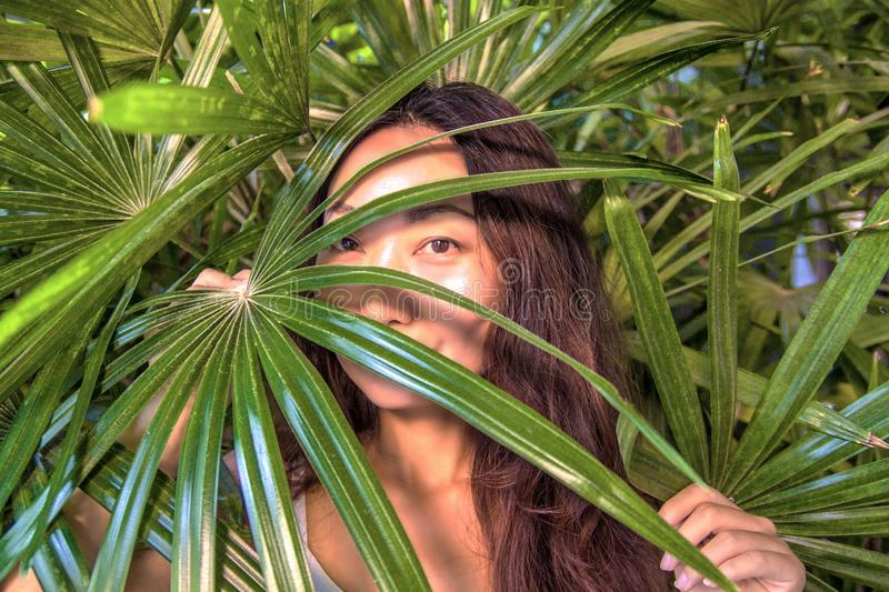 A beautiful woman is hiding behind palm leaves. Eastern beauty and skin care. royalty free stock photos