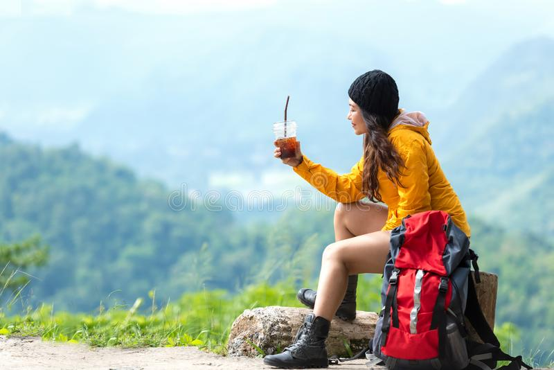 Asian women hiker or traveler with backpack adventure sitting and drinking ice coffee relax and rest on the mountain outdoor for d stock photography