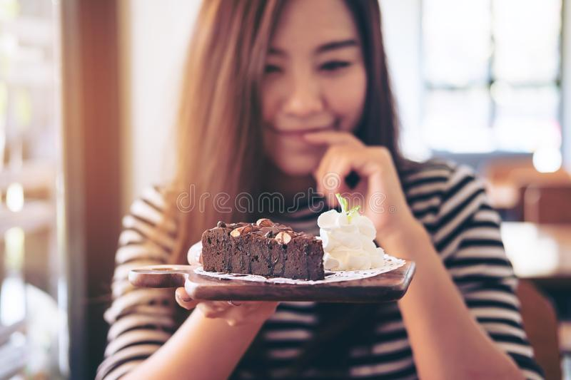 Asian woman holding brownie cake and whipped cream with feeling happy and good lifestyle in the modern cafe. A beautiful asian woman holding brownie cake and stock photography