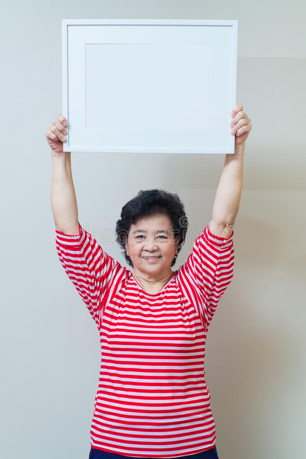 Asian woman holding empty white picture frame in studio shot, sp. Asian woman showing and holding empty white picture frame in studio shot, specialty tones with stock photo