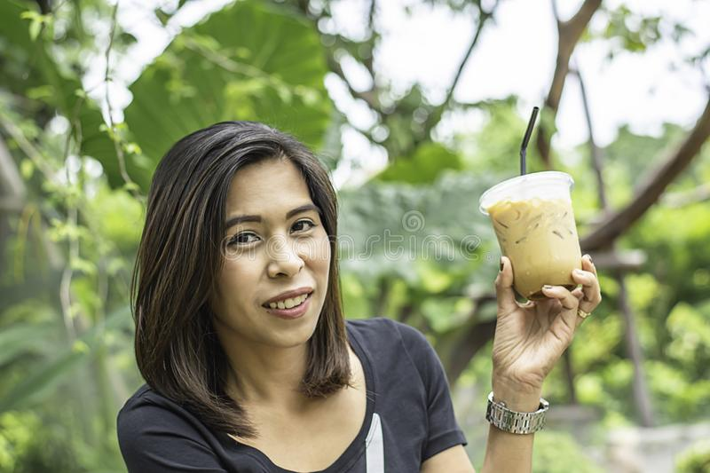 Asian woman holding a glass of cold espresso coffee Background blurry views tree stock image