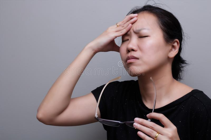 Asian woman holding glasses, suffer from having a strong headache and fever, poor sight, farsightedness, myopia.  stock photos