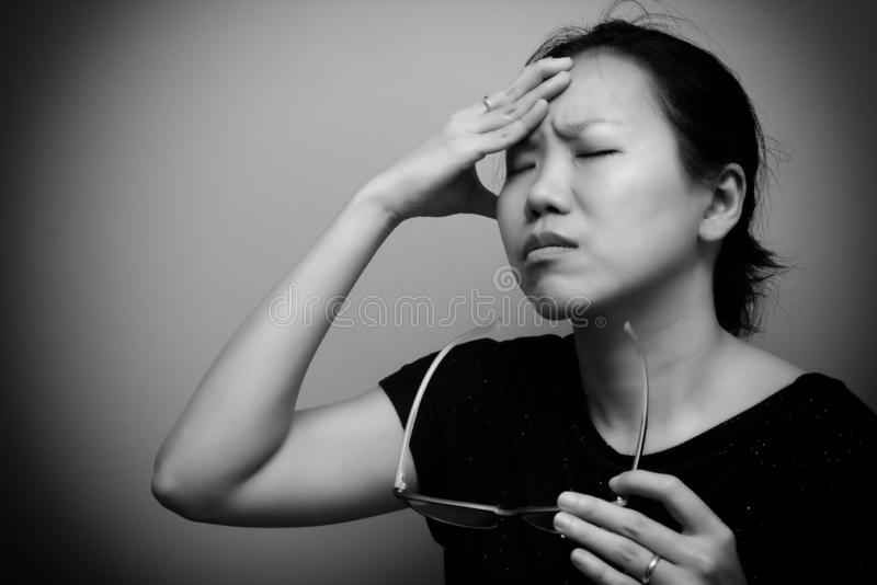 Asian woman holding glasses, suffer from having a strong headache and fever, poor sight, farsightedness, myopia. Black and white. Tone stock photos