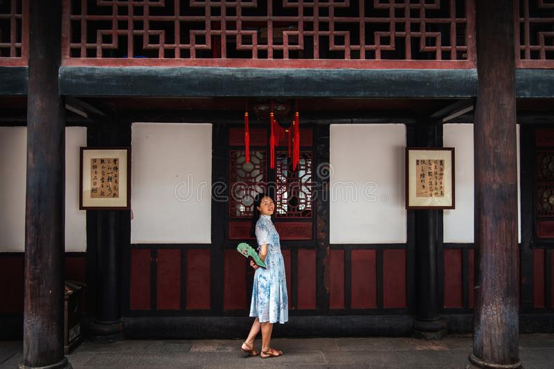 Asian woman in a temple holding a hand fan royalty free stock photo