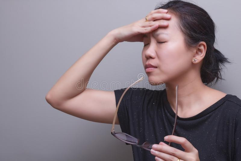Asian woman holding her head, suffer from having a strong headache and fever, poor sight, farsightedness, myopia.  royalty free stock image