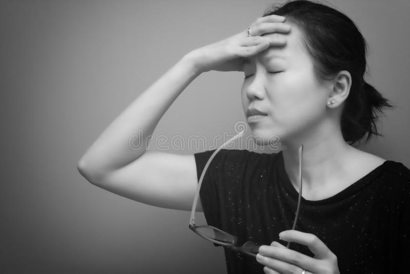 Asian woman holding her head, suffer from having a strong headache and fever, poor sight, farsightedness, myopia. black and white. Tone stock images