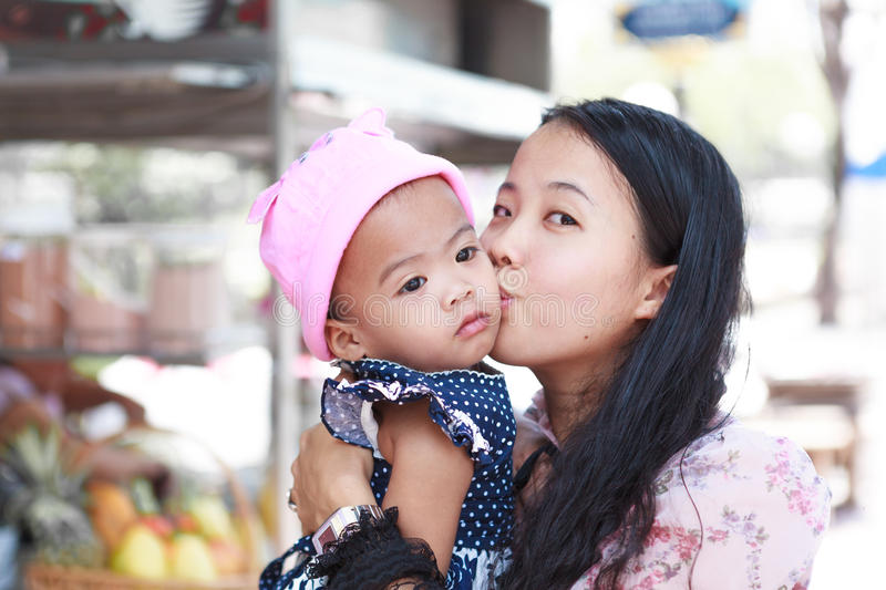 Asian woman holding and kissing baby stock images