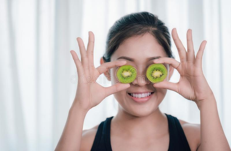 An Asian woman is holding kiwi fruit and enjoying health care. royalty free stock photo