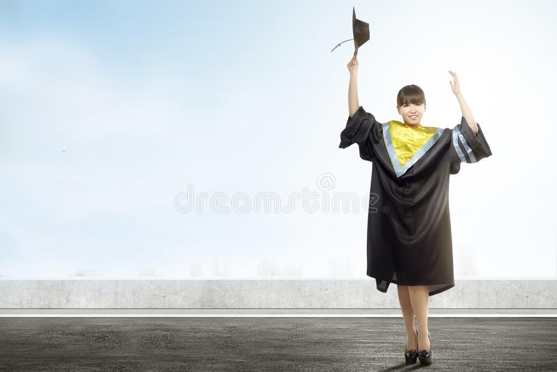 Asian woman holding mortarboard cap celebrate graduation from college. Graduation concept royalty free stock photos