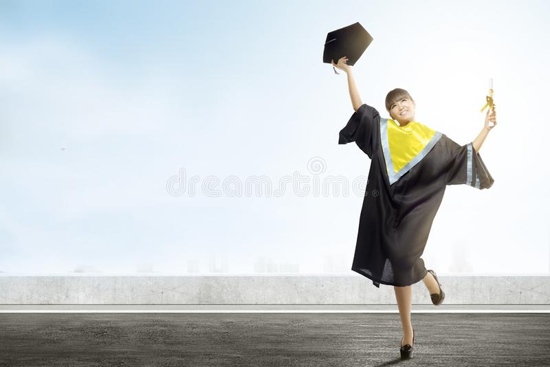 Asian woman holding mortarboard hat and diploma celebrate graduation from college. Graduation concept royalty free stock photo