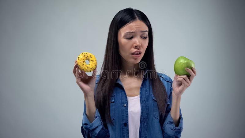 Asian woman holding sweet greasy donut and juicy green apple in hands, decision. Stock photo royalty free stock photo