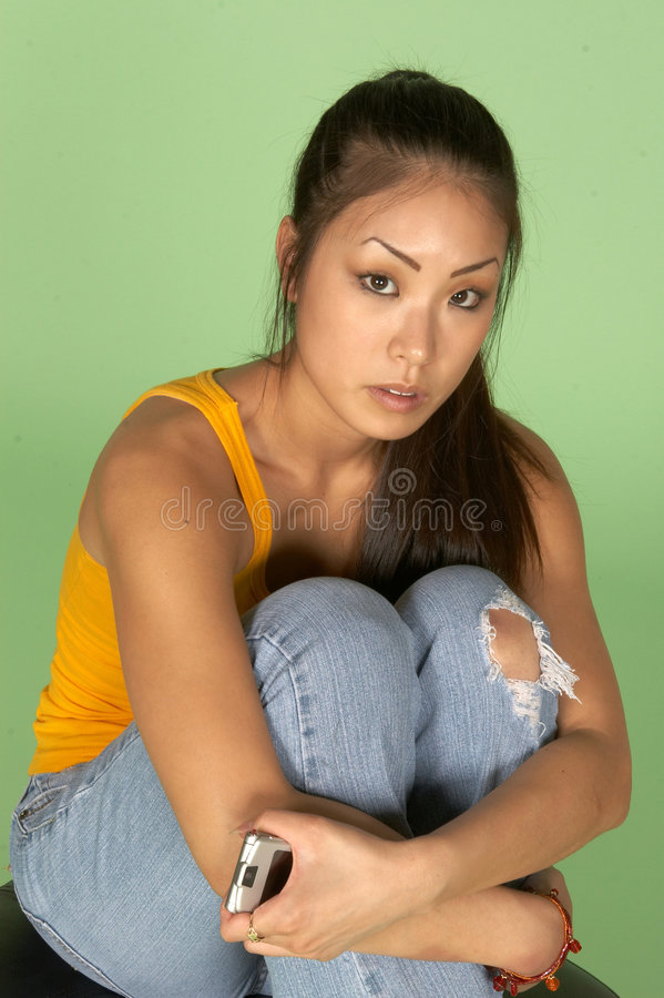 Asian Woman Hugging Knees with Cell Phone stock photo