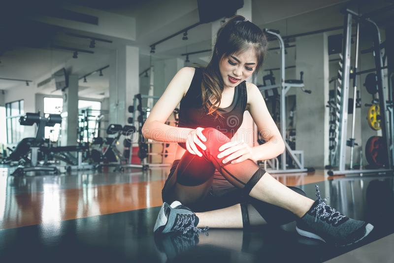 Asian woman injuries during workout at knee in fitness gym. Medical and Healthcare concept. Exercise and Training theme. royalty free stock photos