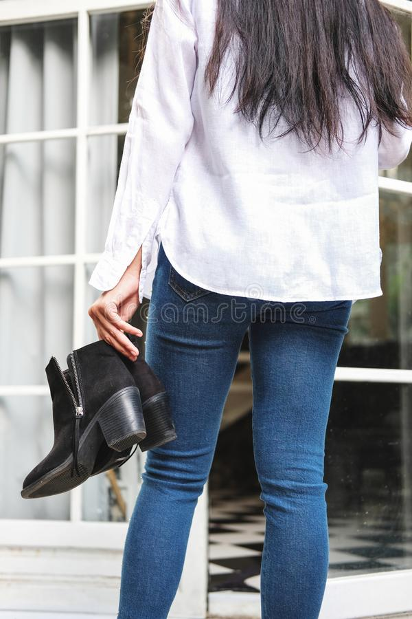 Asian woman in jeans with white tshirt holding black heel shoes royalty free stock image