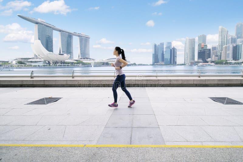 Asian woman jogging on the esplanade bridge stock photography