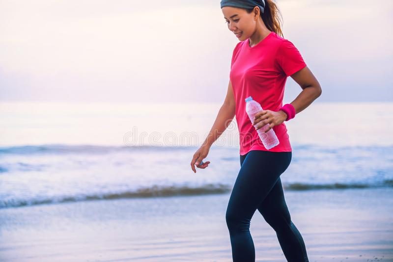 Asian women jogging workout on the beach in the morning. Relax with the sea walk and drinking water from the plastic bottles. Asian woman jogging workout on the royalty free stock photos
