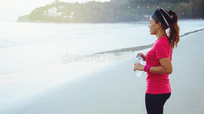 Asian women jogging workout on the beach in the morning. Relax with the sea walk and drinking water from the plastic bottles. Asian woman jogging workout on the royalty free stock images