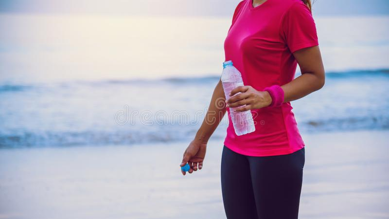 Asian women jogging workout on the beach in the morning. Relax with the sea walk and drinking water from the plastic bottles. Asian woman jogging workout on the royalty free stock photo