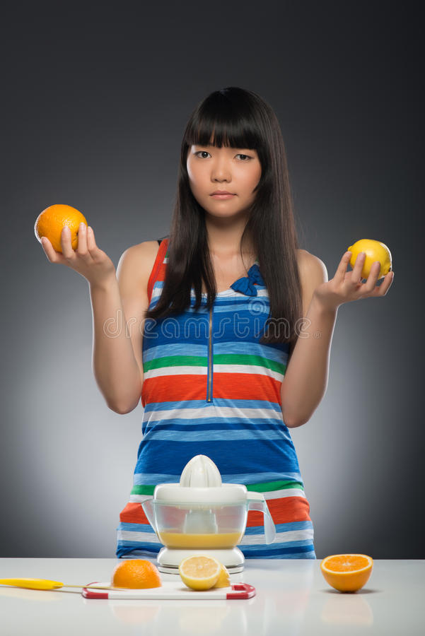 Asian woman and juice. Half-length portrait of young smiling dark-haired Asian woman standing at the table with juicer on it holding orange in one hand and lemon stock image