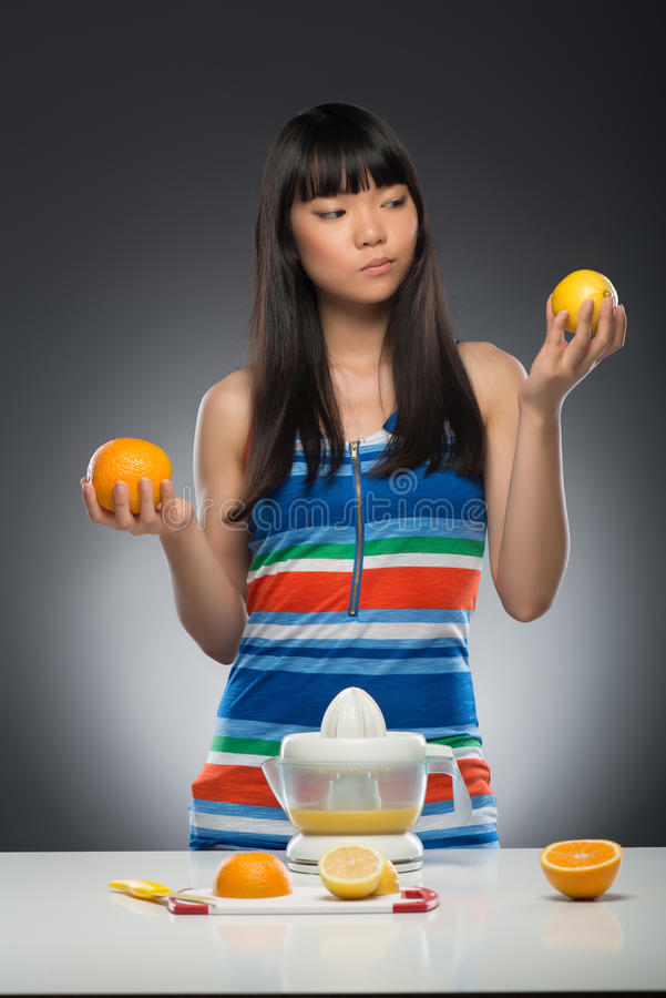 Asian woman and juice. Half-length portrait of young smiling dark-haired Asian woman standing at the table with juicer on it holding orange in one hand and lemon royalty free stock image