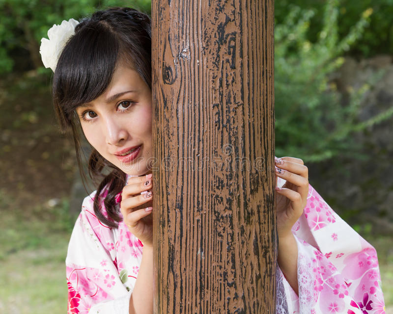 Asian woman in kimono behind wooden pillar royalty free stock photo