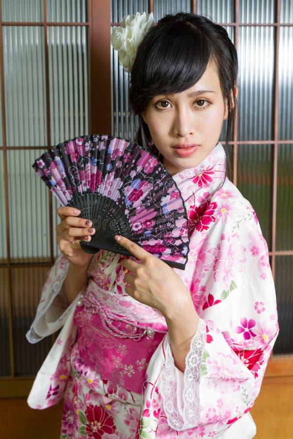 Asian woman in kimono holding fan royalty free stock image
