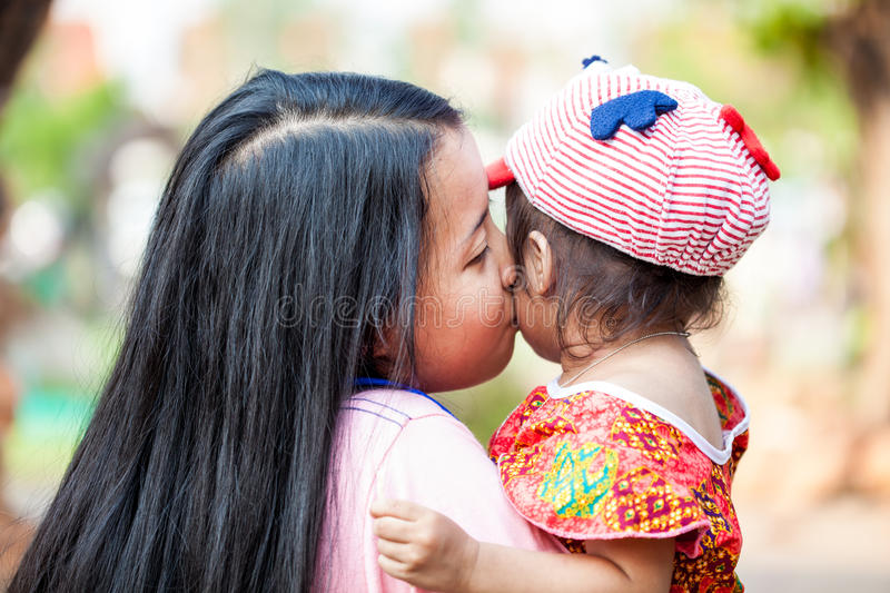 Asian woman kissing her daughter royalty free stock image