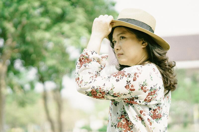 Asian woman lady wear a hat to travel in vacation at park stock photos