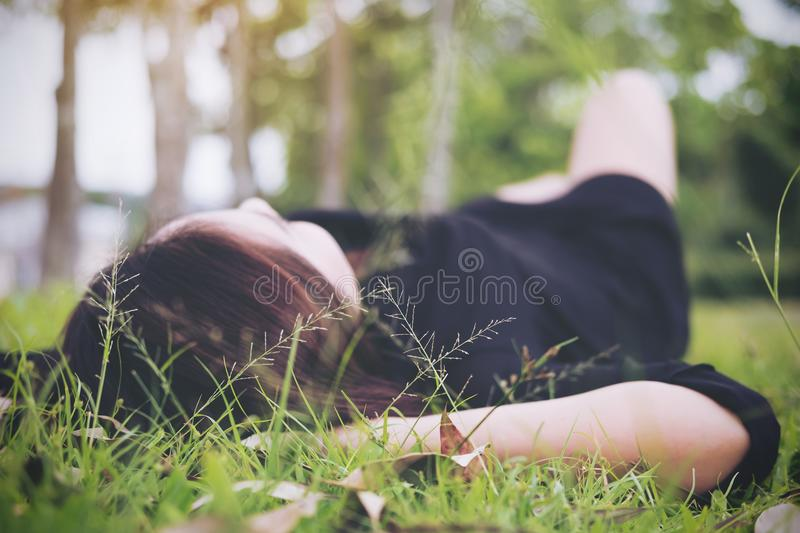 An Asian woman lay down on grass field with feeling relax and green nature stock photo
