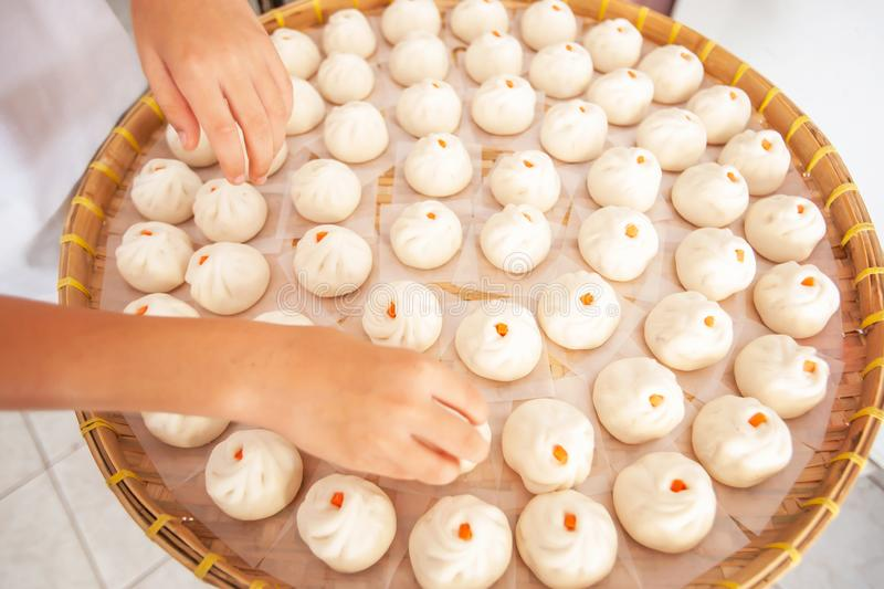 Asian woman is laying Baozi or Bun on bamboo basket. In a typical Chinese home, close shot of woman hands is laying Baozi. Homemade food. Food culture stock photos