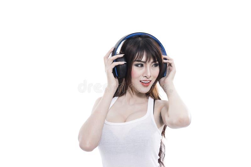 Asian woman listen music via wireless headphone royalty free stock photos