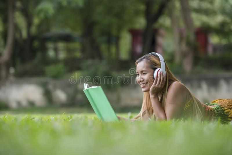 Asian woman listening favorite music on headphones and reading a book. Happy time stock photo