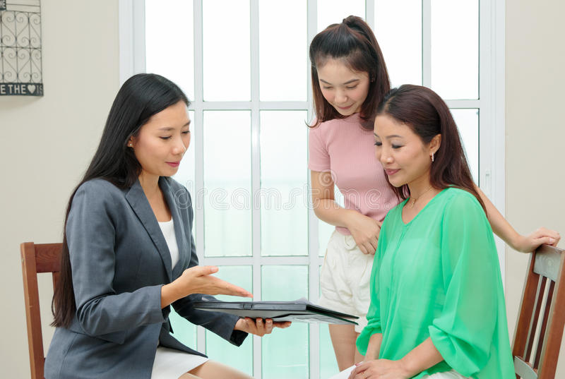 Asian woman listens to a saleswoman or insurance consultant sitting at table in home stock photo