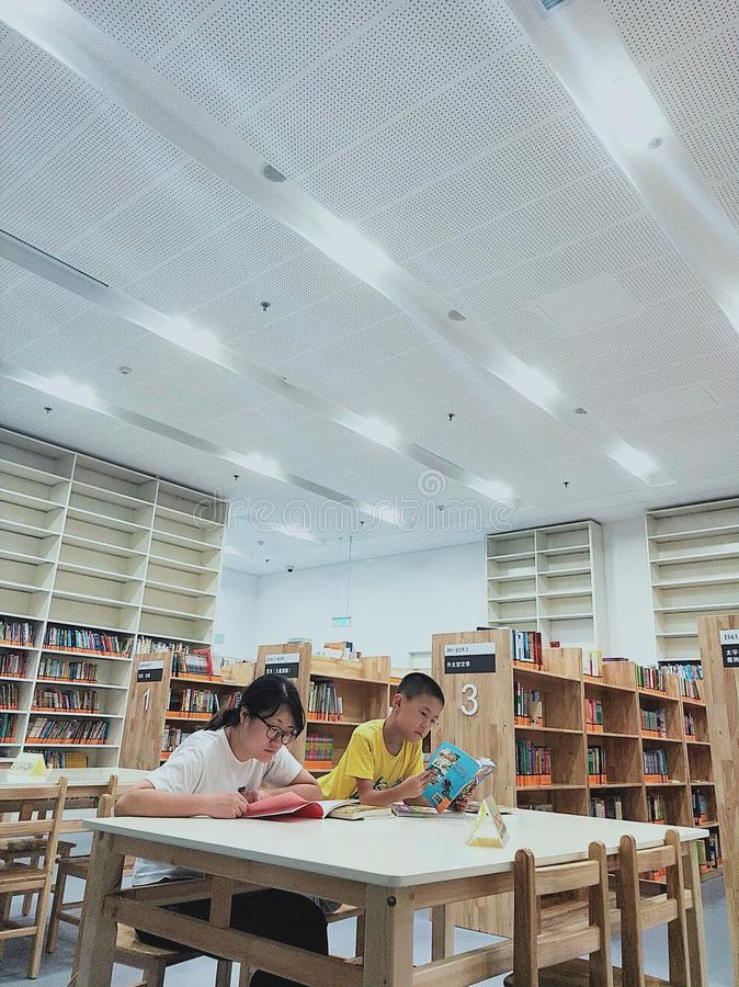An Asian woman and a little boy who are reading royalty free stock photos
