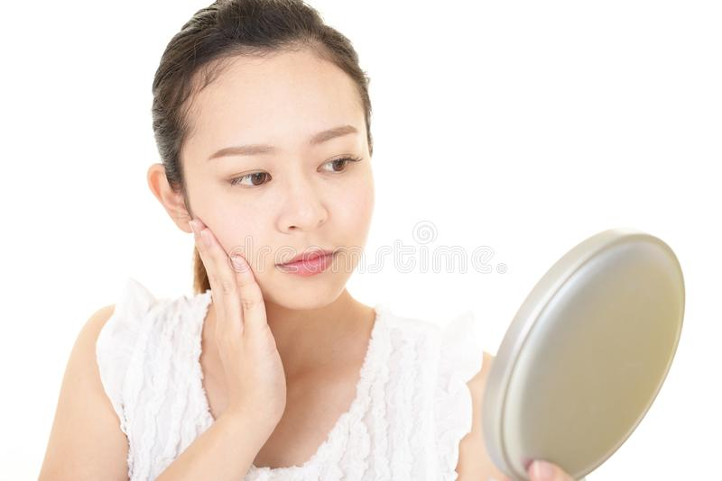 Asian woman looking at her face in mirror royalty free stock photos