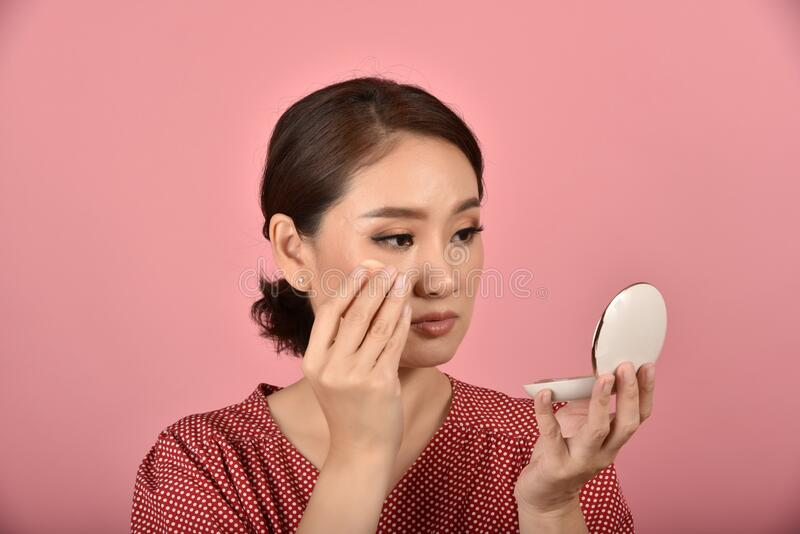 Asian woman looking at her facial problem in the mirror, Female feeling annoy about her reflection appearance show the aging skin. Asian woman looking at her royalty free stock images