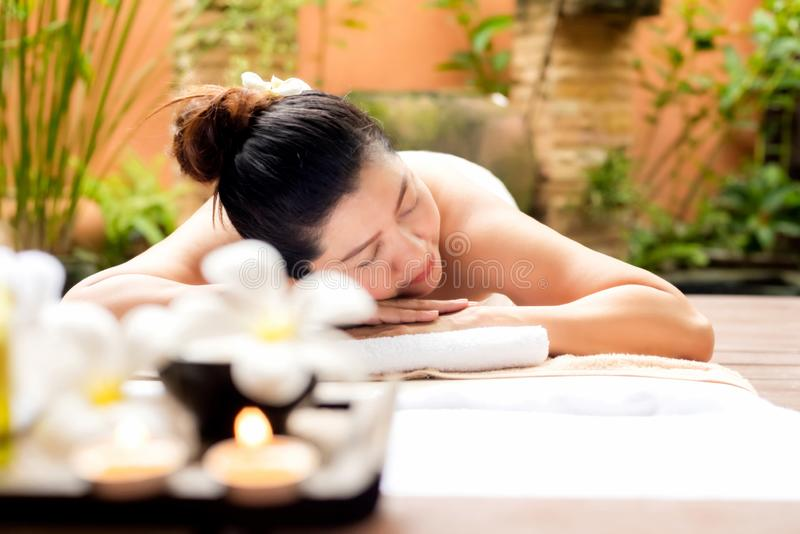 Asian woman lying down on massage bed with scrub sugar and salt aroma at outdoor natural.  wellness center, so relax and lifestyle stock photography