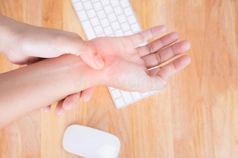 Asian woman massaging painful hand, office syndrome concept royalty free stock photo