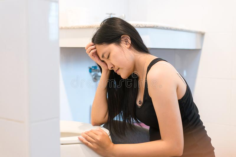 Asian woman with morning sickness,Pregnant female nausea in toilet. Asian woman with morning sickness,Pregnant female nausea in a toilet royalty free stock image