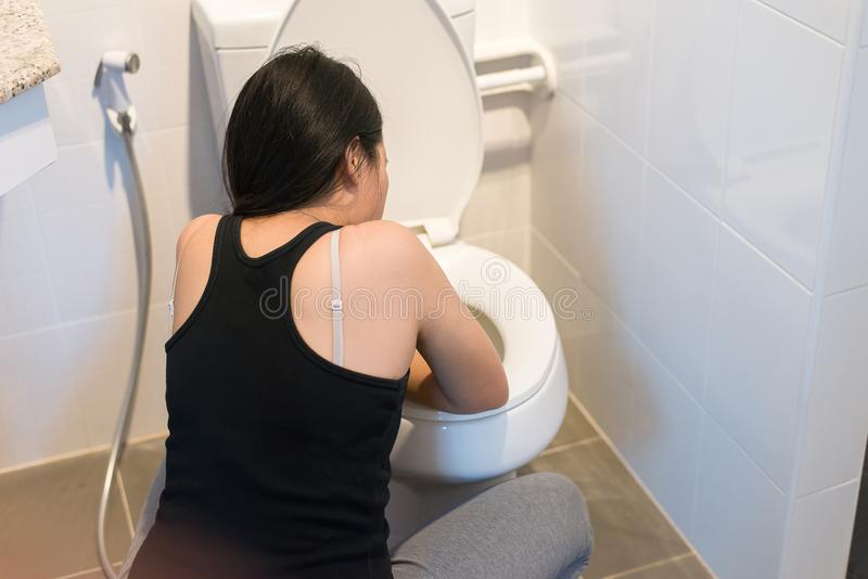 Asian woman with morning sickness,Pregnant female nausea in toilet. After wake up royalty free stock images