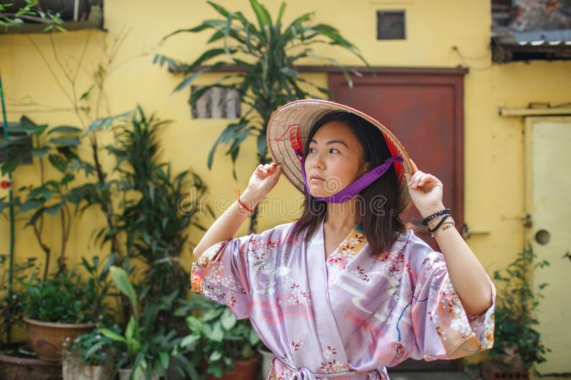 An Asian woman in a non la hat is photographed against a yellow wall royalty free stock photos