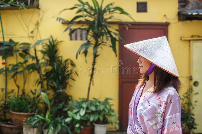 An Asian woman in a non la hat is photographed against a yellow wall royalty free stock photography