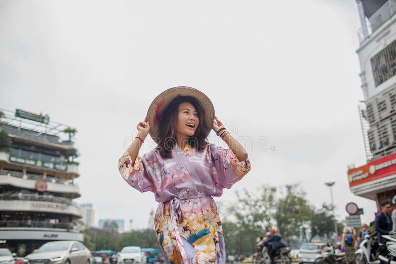 An Asian woman in a non la hat is photographed against a yellow wall. Near which plants grow. Hands girl holds hat and looks away royalty free stock images