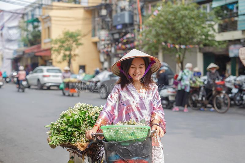 An Asian woman in a non la hat is photographed against a yellow wall. Near which plants grow. Hands girl holds hat and looks away royalty free stock photo