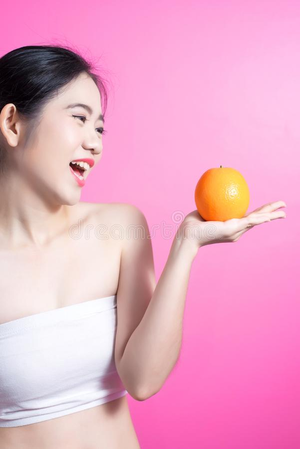 Asian woman with orange concept. She smiling and holding orange. Beauty face and natural makeup. Isolated over pink background. royalty free stock image