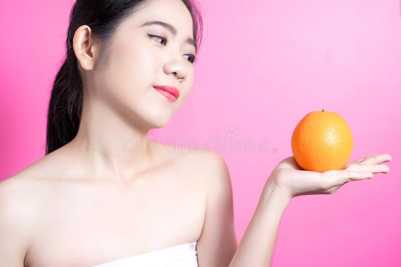 Asian woman with orange concept. She smiling and holding orange. Beauty face and natural makeup. Isolated over pink background. stock photography